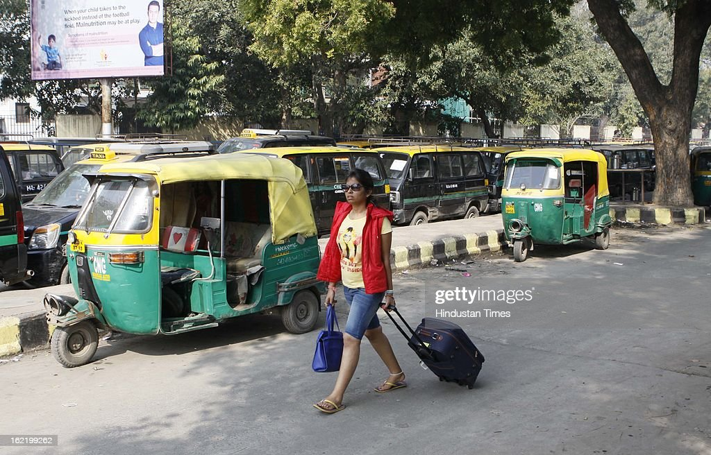 A passenger walking with her luggage as auto-rickshaw and taxis refuse to come on road in support of 48 hour nationwide strike called by 11 Central Trade Unions on February 20, 2013 in New Delhi, India. The strike called against UPA's economic and alleged anti-labour policies crippled financial services like banks and insurance companies. Transport sector was partially hit by the strike as many bus, auto-rickshaw and taxi unions also extended their support.