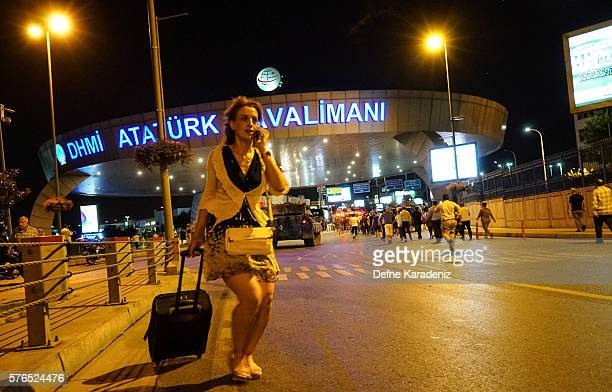 A passenger walks as Turkish army's tanks enter the Ataturk Airport on July 16 2016 in Istanbul Turkey Istanbul's bridges across the Bosphorus the...