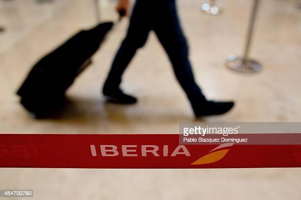 A passenger walks at Iberia's checkin area at Adolfo Suarez Madrid Barajas Airport on September 5 2014 in Madrid Spain Iberia British Airway's...
