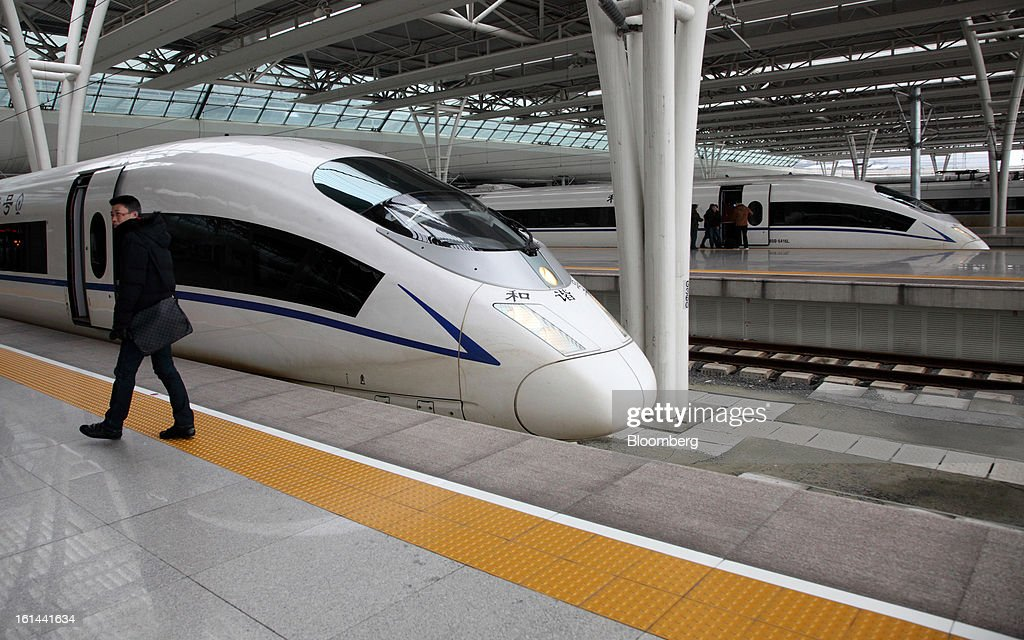 A passenger walks near a China Railways high speed train parked at Hongqiao Railway Station in Shanghai, China, on Friday, Feb. 8, 2013. A record 3.41 billion passenger trips may be made this year during the Lunar New Year period, according to the National Development and Reform Commission. Photographer: Tomohiro Ohsumi/Bloomberg via Getty Images