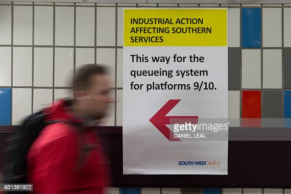 A passenger walks next to a information board pointing passengers toward a special queueing system for operating platforms at at Clapham Junction...