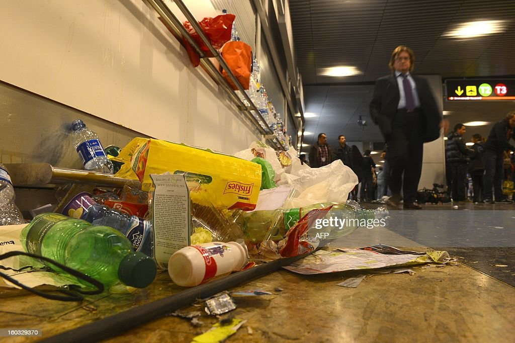 A passenger walks next to uncollected garbage at Barajas airport in Madrid on January 29, 2013. Garbage piled up at Madrid's Barajas airport, one of Europe's busiest, due to a strike by cleaning staff over salary cuts and job losses. MARCOU