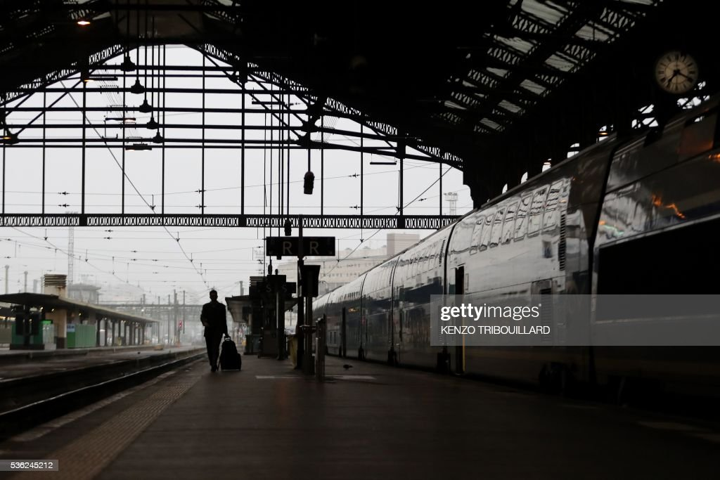 A passenger walks on a platform at the Gare de Lyon railway station on June 1, 2016 in Paris, at the start of a strike by employees of French state-owned rail operator SNCF to protest against government labour reforms. Rail strikes in France are expected to take full effect, disrupting transport across the country just over a week before the Euro 2016 football championship starts. / AFP / KENZO