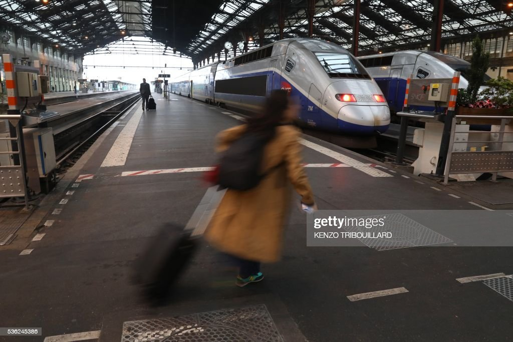 A passenger walks on June 1, 2016 at the Gare de Lyon railway station in Paris, at the start of a strike by employees of French state-owned rail operator SNCF to protest against government labour reforms. Rail strikes in France are expected to take full effect, disrupting transport across the country just over a week before the Euro 2016 football championship starts. / AFP / KENZO