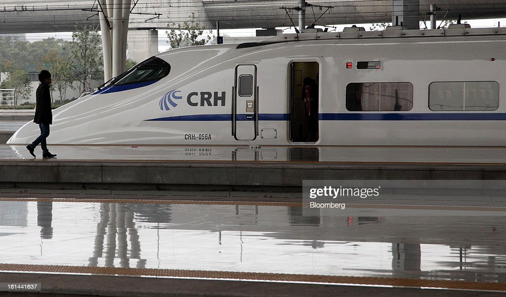 A passenger walks past a China Railways high speed train parked at Hongqiao Railway Station in Shanghai, China, on Friday, Feb. 8, 2013. A record 3.41 billion passenger trips may be made this year during the Lunar New Year period, according to the National Development and Reform Commission. Photographer: Tomohiro Ohsumi/Bloomberg via Getty Images