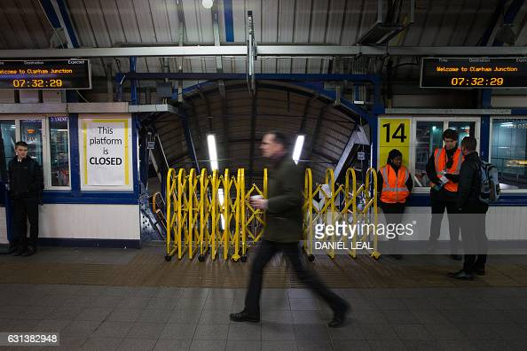 A passenger walks past a closed entrance to a platform used by Southern Rail at Clapham Junction station in London on January 10 2017 during a...