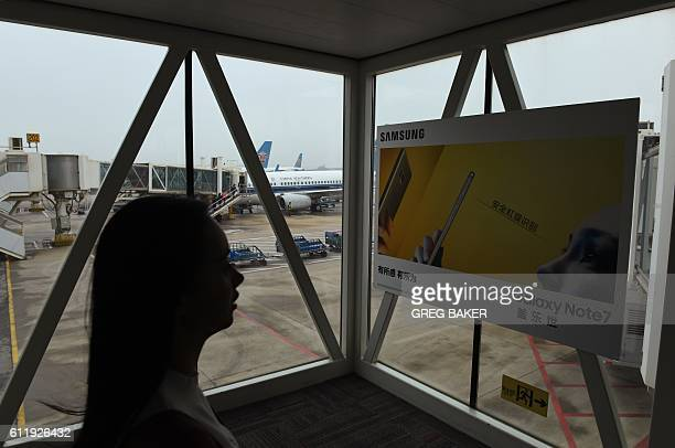 A passenger walks past an advertisement for the Samsung Galaxy Note 7 smartphone on an air bridge leading to a plane at the airport in Wuhan in...