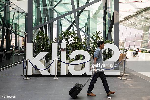 A passenger walks past signage for Kuala Lumpur International Airport 2 at the airport in Sepang Malaysia on Tuesday June 24 2014 KLIA2 will provide...