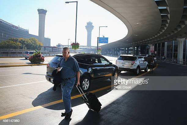 A passenger walks through O'Hare International Airport on September 26 2014 in Chicago Illinois All flights in and out of Chicago's O'Hare and Midway...