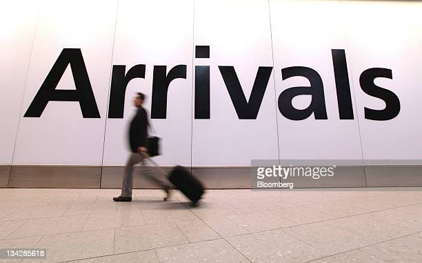 A passenger walks through the arrivals hall in Terminal 4 at Heathrow airport during a one day publicsector workers strike in London UK on Wednesday...