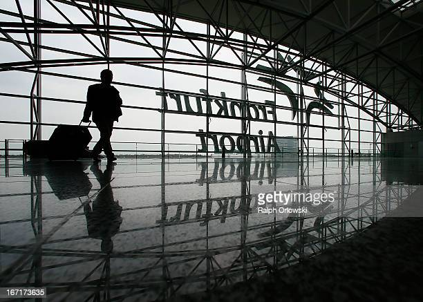 A passenger walks through the Frankfurt airport during a nationwide protest of Lufthansa ground personnel at Frankfurt Airport on April 22 2013 in...