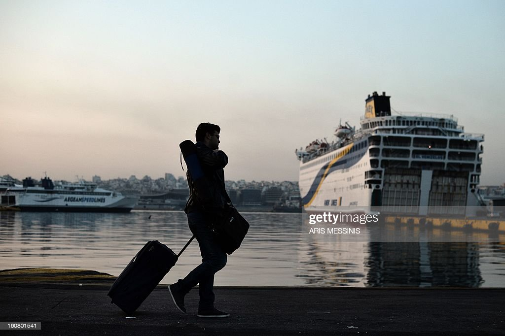 A passenger walks to a police protected embarkment area of Greece's main harbour Piraeus port early on February 6, 2013 in Athens during the forced end to a strike movement by seamen. Riot police were sent to Greece's main harbour Piraeus early today to end a strike by seamen that has disrupted ferry services to the country's myriad islands for nearly a week, enforcing an emergency government order that took effect at 0400 GMT to force the strikers back to work. AFP PHOTO / ARIS MESSINIS
