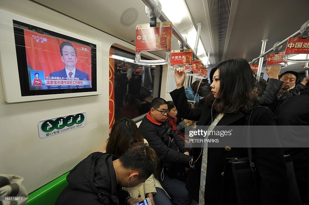 A passenger (R) watches Chinese Premier Wen Jiabao (Top-L) speaking at the opening session of the National People's Congress (NPC), on a subway train in Shanghai on March 5, 2013. Premier Wen targeted 2013 growth of 7.5 percent and vowed an unwavering fight against corruption as the world's second-largest economy opened its annual parliamentary session. AFP PHOTO/Peter PARKS