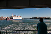 A passenger watches from an incoming ferry as the Wightlink ferry St Cecilia leaves Portsmouth harbour and heads across the Solent to the Isle of...