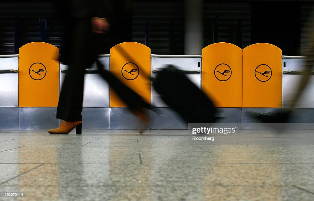 A passenger wheels a suitcase past the Deutsche Lufthansa AG service desks at Frankfurt airport in Frankfurt, Germany, on Thursday, March 14, 2013. Deutsche Lufthansa AG agreed to renew its short-haul fleet with 100 mostly fuel-efficient jets from Airbus SAS, as the airline seeks to cut kerosene costs that constitute its single biggest expense. Photographer: Ralph Orlowski/Bloomberg via Getty Images
