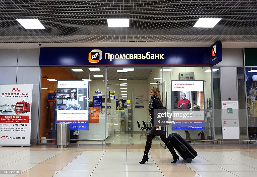 A passenger wheels her luggage past a branch of OAO Promsvyazbank at Sheremetyevo airport in Moscow, Russia, on Wednesday, Nov. 28, 2012. Bank Rossii proposes government create rule limiting increases of budget funds held at central bank, RIA Novosti reports, citing First Deputy Chairman Alexey Ulyukayev. Photographer: Andrey Rudakov/Bloomberg via Getty Images