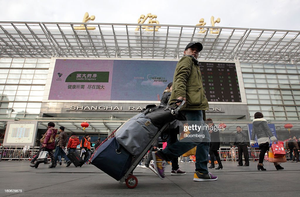 A passenger wheels his luggage as he arrives at Shanghai Railway Station in Shanghai, China, on Sunday, Feb. 3, 2013. Forecasts of snow and rain across China threaten to disrupt the travel plans of millions of Chinese heading home for the Lunar New Year holidays that start Feb. 9, the national weather agency warned. Photographer: Tomohiro Ohsumi/Bloomberg via Getty Images