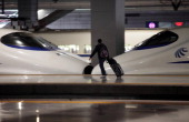 A passenger wheels his luggage past a China Railways high speed train at Hongqiao Railway Station in Shanghai China on Friday Feb 8 2013 A record 341...