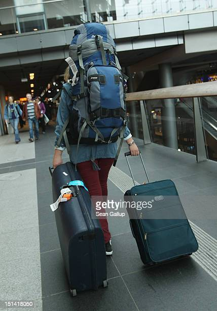 A passenger with Tegel airport luggage tickets atttached to her backpack and suitcase walks toward platforms at Hauptbahnhof train station during a...