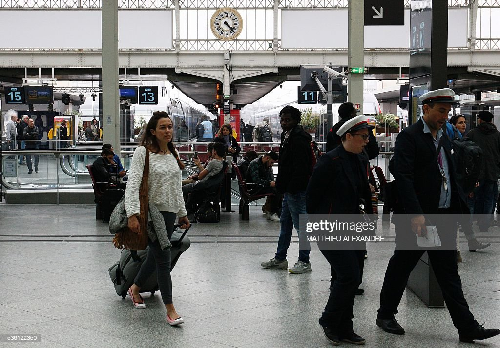 Passengers and station employees walk in the Gare de Lyon rail station in Paris, on May 31, 2016, a few hours prior to the start of a strike by employees of French state-owned rail operator SNCF to protest against government labour reforms. France is bracing for a week of severe disruption to transport after unions called for more action in their bitter standoff with the Socialist government over its labour market reforms. / AFP / MATTHIEU