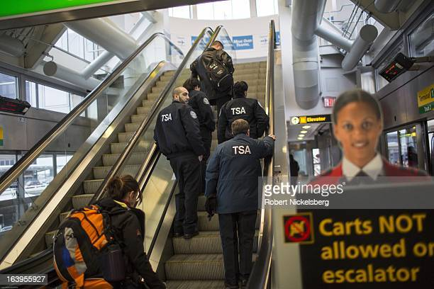 Passengers and Transportation Safety Administration employees ride an escalator to a terminal at the John F Kennedy International Airport February 26...