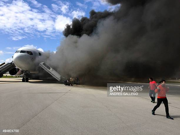 Passengers are evacuate from a plane on fire at Fort Lauderdale airport Florida on October 29 2015 An airliner caught fire on a runway at Fort...