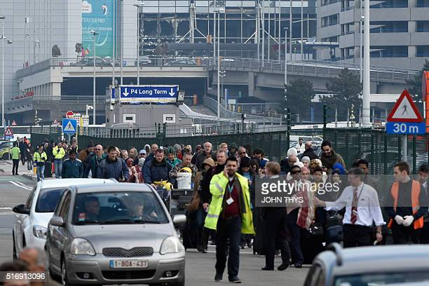 Passengers are evacuated from Brussels airport on March 22 2016 in Zaventem after at least 13 people were killed and 35 injured as twin blasts rocked...