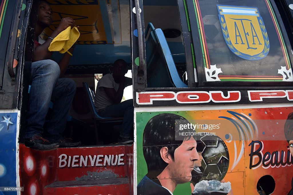 Passengers are seat on a Tap Tap, public transportation vehicle that have painted face of Argentinian football player Lionel Messi and the coat of the AFA (Argentine Football Association), in Port-au-Prince on May 27, 2016. Haiti will play Brazil, Ecuador, and Peru in the upcoming COPA America Centerario soccer tournament in the United States taking place between June 3 and June 26, 2016. / AFP / HECTOR
