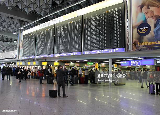 Passengers are seen at the Frankfurt Airport as German airline Lufthansa suspends more than half of its flights in Frankfurt am Main Germany on March...