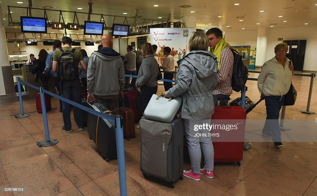 Passengers arrive at a temporary check-in area during the partial reopening of the departure hall of Brussels Airport in Zaventem on May 1, 2016, after it was badly damaged in twin suicide attacks on March 22, that killed 16 people. A total of 32 people were killed and more than 300 wounded in coordinated suicide bombings at the airport and a metro station in central Brussels on March 22 in Belgium's worst ever terror attacks. / AFP / JOHN