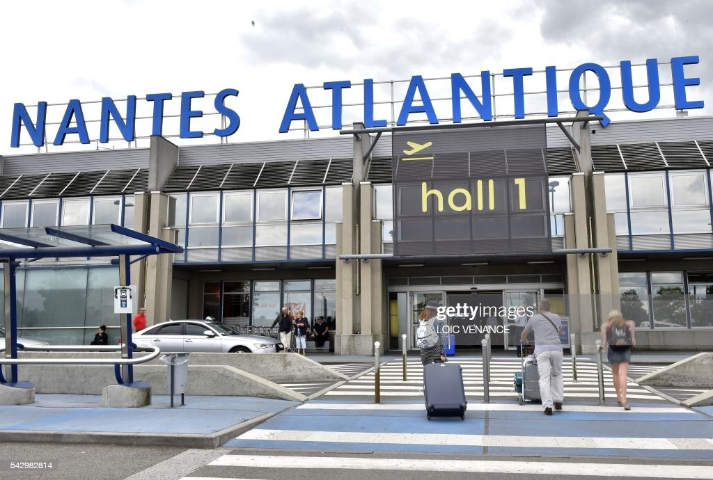 Passengers arrive at the Nantes-Atlantique airport in Bouguenais, suburb of Nantes, on June 25, 2016, the day before a local referendum organized in Loire Atlantique to transfer of the Nantes Atlantique airport to Notre-Dame-des-Landes. / AFP / LOIC