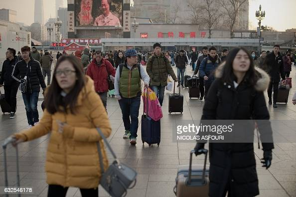 Passengers arrive at the train station as they prepare to travel to their hometowns for the 'Spring Festival' or Lunar New Year on January 24 2017 at...