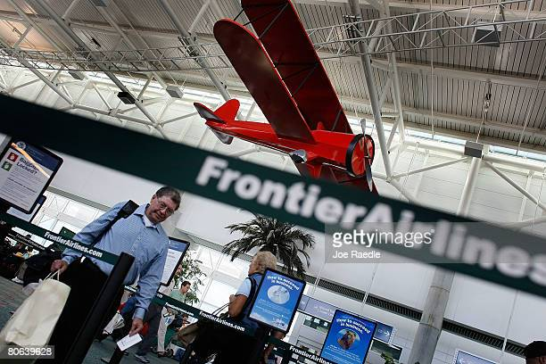 Passengers arrive to check in at the ticket counter for Frontier Airlines April 11 2008 at the Fort Lauderdale/Hollywood International airport in...