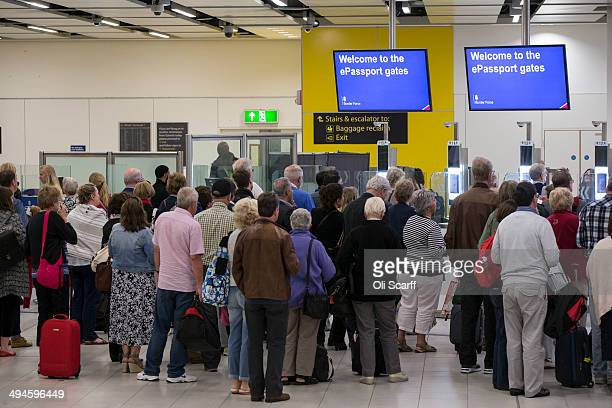Passengers arriving at Gatwick Airport use the 'ePassport gates' at Passport Control on the UK Border on May 28 2014 in London England Border Force...