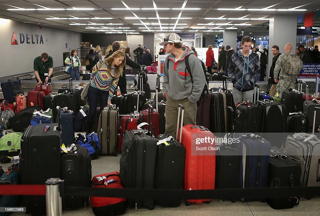 Passengers arriving at O'Hare International Airport search for their luggage on December 21, 2012 in Chicago, Illinois. Today is the busiest air travel day of the Christmas holiday, with an estimated 200,000 travelers expected to travel through O'Hare today.