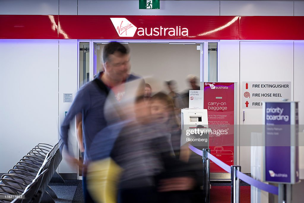 Passengers arriving on a flight operated by Virgin Australia Holdings Ltd. exit a gate at the domestic terminal of Sydney Airport in Sydney, Australia, on Thursday, Aug. 29, 2013. Virgin will make a net loss in the range of A$95 million to A$110 million when it reports annual results tomorrow, the Brisbane-based carrier forecast Aug. 5. Photographer: Ian Waldie/Bloomberg via Getty Images