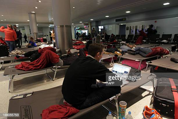Passengers at New York's John F Kennedy International Airport remain stranded on October 31 2012 even as the airport resumes some service after being...