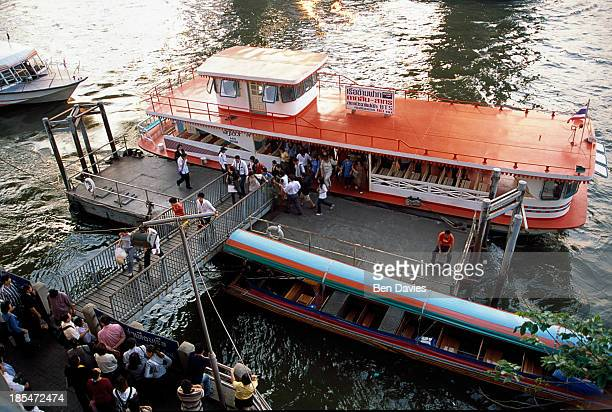 Passengers at Sathorn Bridge board a river ferry on the Chao Phya River known as the River of Kings Despite so much new construction old rice barges...