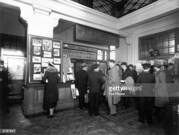 Passengers at the Air France counter at Croydon Airport A sign advertises oneandahalfhour flights from London to Paris at a price of six guineas...