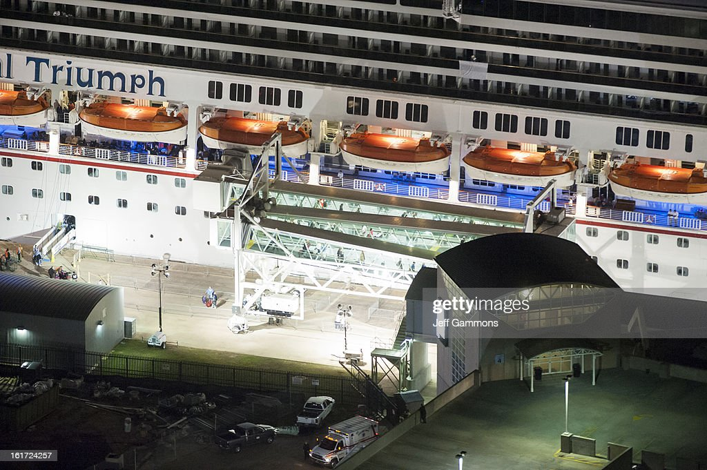 Passengers begin to disembark from the crippled cruise liner Carnival Triumph February 14, 2013 in Mobile, Alabama. An engine fire on February 10 left the ship and its 4,000 passengers without power and with scarce food, according to passengers onboard. While passengers reported toilets that wouldn't work, the ship was restocked with food during the days it was being towed through the Gulf of Mexico. According to reports, a few dozen people awaited the ship's arrival in Mobile, covered live by cable news network CNN.