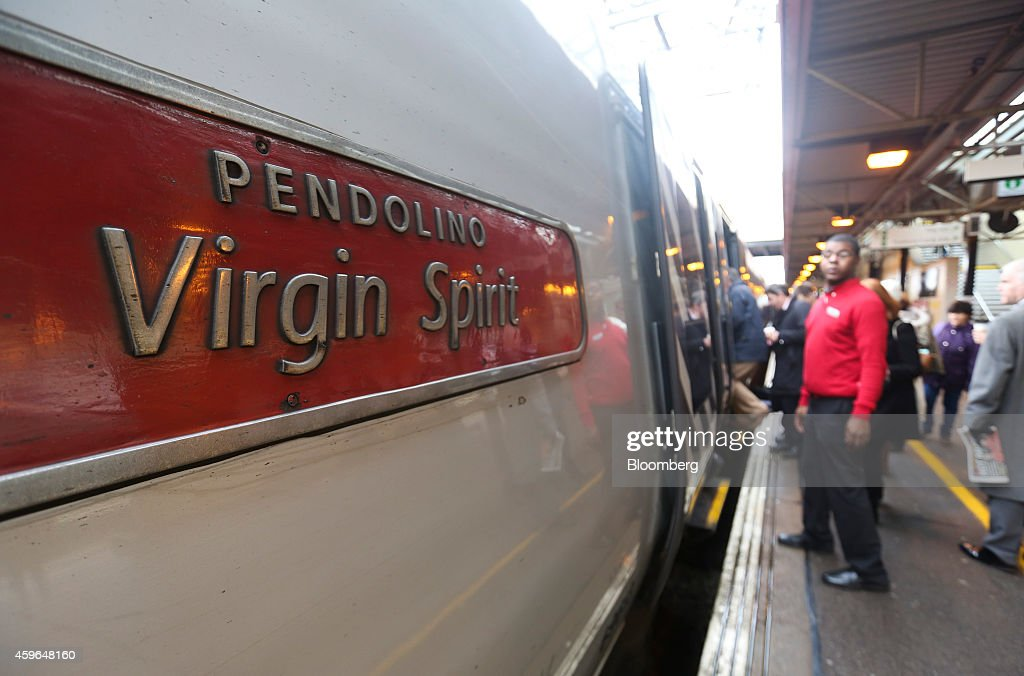 Passengers board a Pendolino West Coast train, operated by Virgin Trains, as it stands beside a platform at Milton Keynes railway station in Milton Keynes, U.K., on Thursday, Nov. 27, 2014. Virgin Trains and partner Stagecoach Group Plc were chosen to run the London-Edinburgh rail route, fending off rival bids from FirstGroup Plc and Eurostar International Ltd. and delivering a boost for Richard Branson a month after the fatal crash involving his space venture. Photographer: Chris Ratcliffe/Bloomberg via Getty Images