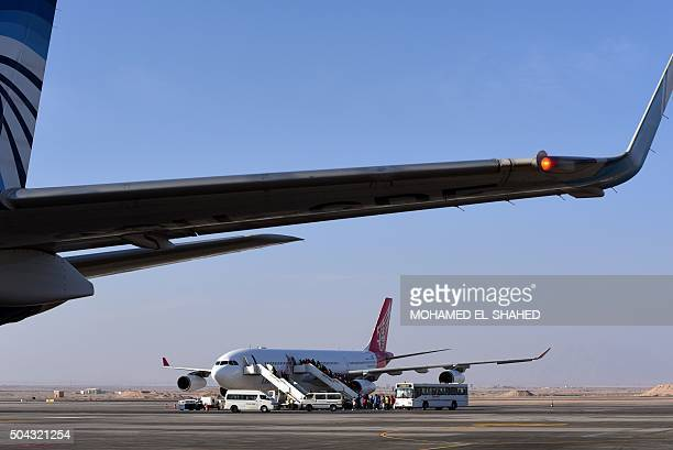 Passengers board a plane at the Hurghada International Airport in Egypt's Red Sea resort on January 10 2016 Two men carrying knifes stormed the...