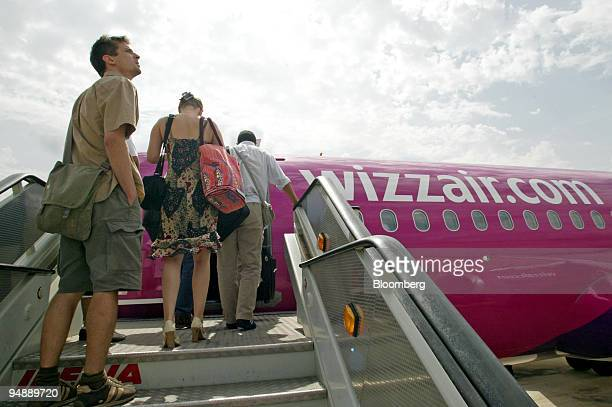 Passengers board a Wizz Air airplane on the tarmac at Gerona International Airport in Gerona Spain Frdiay September 2004 Wizz Air whose fares are...