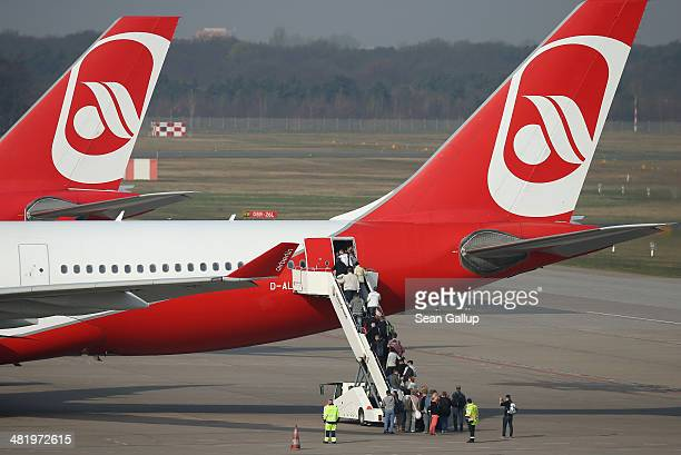 Passengers board an Air Berlin passenger plan at Tegel Airport on April 2 2014 in Berlin Germany Air Berlin is partially owned by Etihad airline and...