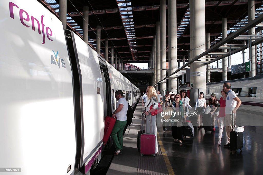 Passengers board an Alta Velocidad Espanola (AVE) high-speed train operated by Renfe Operadora SC as it sits at a platform at Atocha train station in Madrid, Spain, on Saturday, Aug. 3, 2013. Spain's state-owned rail operator Renfe plans to cut almost 500 jobs, or 4% of staff, as early as this year, ABC reports, citing comments by Public Works Minister Ana Pastor. Photographer: Antonio Heredia/Bloomberg via Getty Images