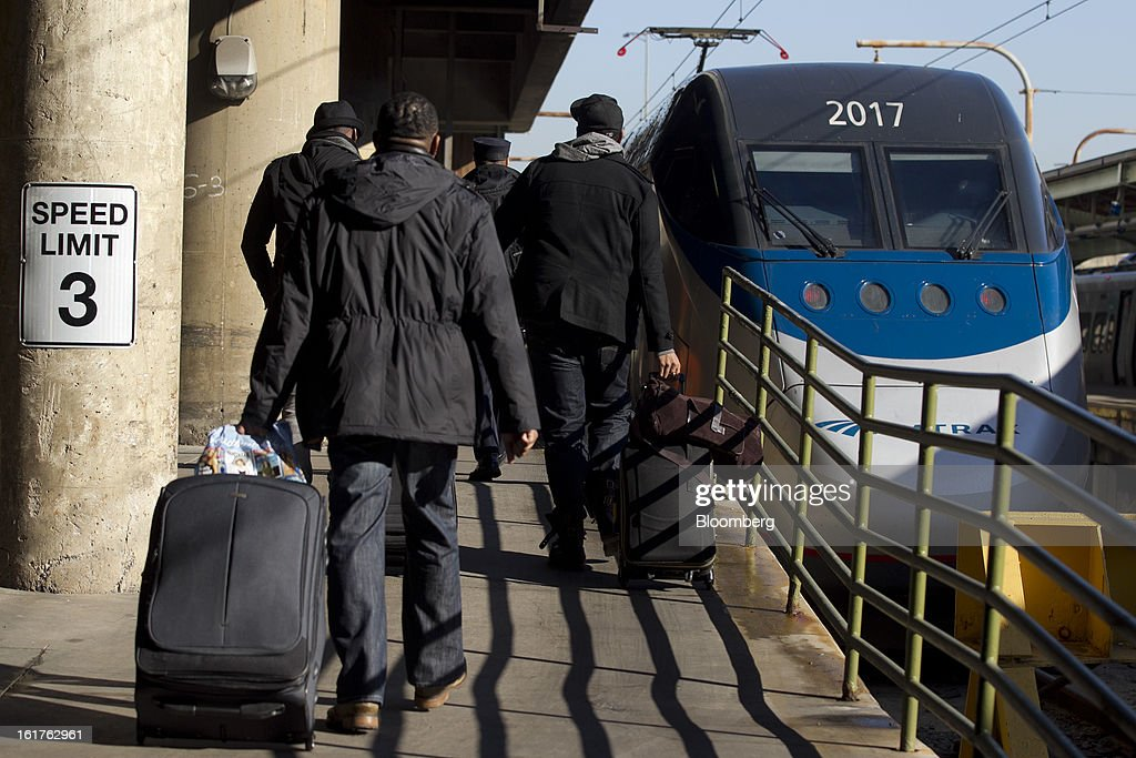 Passengers board an Amtrak Acela train at Union Station in Washington, D.C., U.S., on Friday, Feb. 15, 2013. Amtrak, the U.S. long-distance passenger railroad and federally subsidized since its beginning 41 years ago, last month reported its lowest operating loss in nearly four decades, announcing the passenger rail company had reduced its total operating loss by 19 percent compared to the previous year. Photographer: Andrew Harrer/Bloomberg via Getty Images