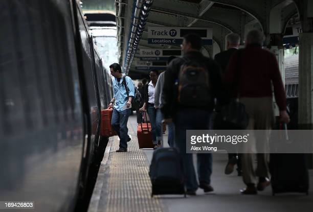 Passengers board an Amtrak train at Union Station May 24 2013 in Washington DC More than 34 million Americans are expected to travel over this...