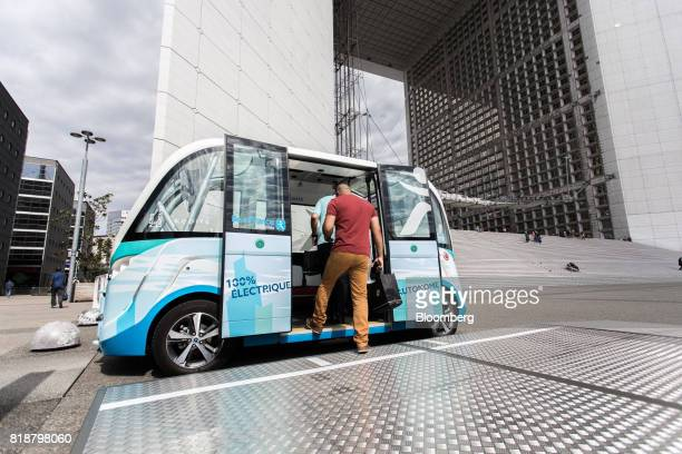 Passengers board an Arma autonomous shuttle bus manufactured by Navya Technologies SAS as the Grande Arche monument stands beyond in La Defense...