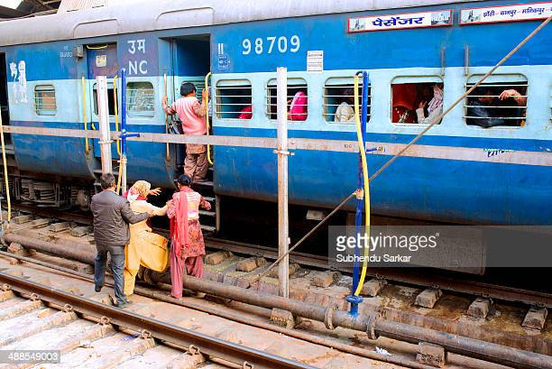Passengers boarding a train from the other side of a railway platform Indian Railways is owned and operated by the government of India It is one of...