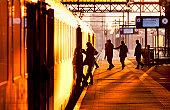 Passengers boarding train at sunset